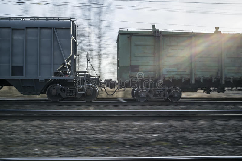 Panning of a freight train on the railway at sunset. Panning a freight train on the railway in the spring evening, at sunset royalty free stock images