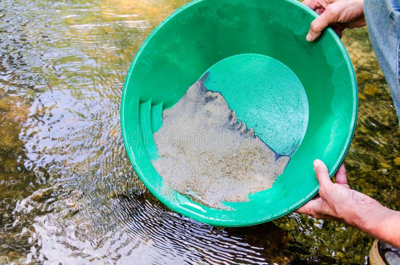 Gold panning in mineral rich stream. Panning for gold in mineral rich stream. Fun, recreational outdoor activity of prospecting for gold and gemstones royalty free stock photos