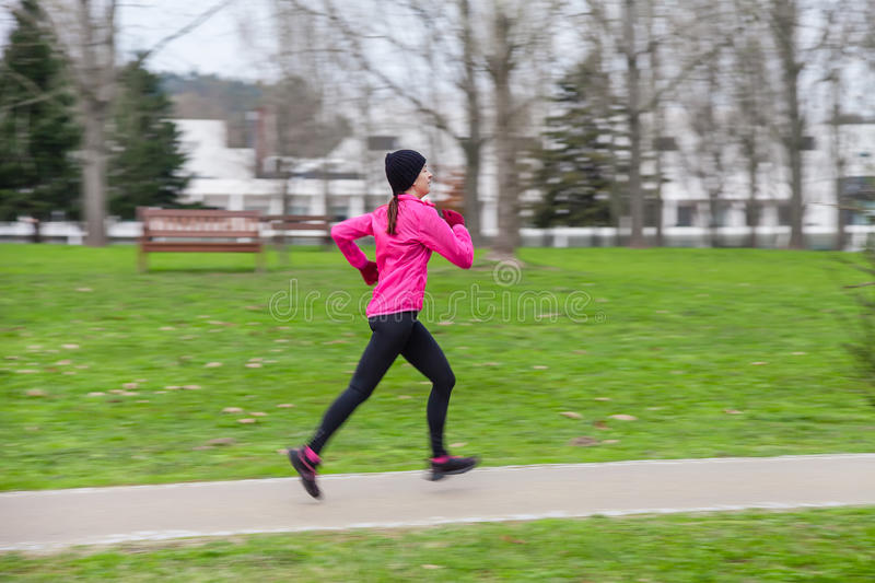 Panning image with motion blur of a young woman running. On a cold winter day on an urban park. Profile or side view royalty free stock photos