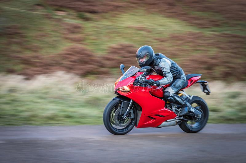Panning Motorbike at Speed. To create motion blur on a country road in Upper Coquetdale, Northumberland royalty free stock image