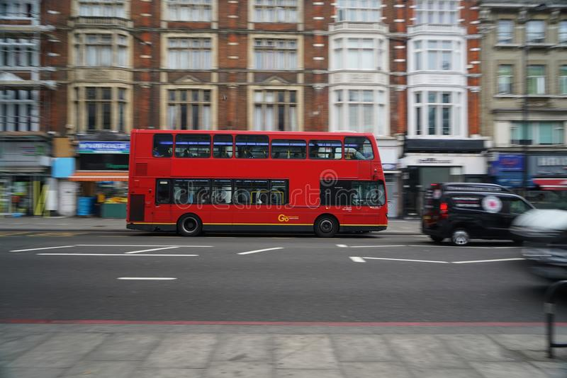 Panning shot of double-decker bus running on Edgware Road early in the morning. London,United Kingdom-May 30, 2017:A double-decker bus is a bus that has two royalty free stock images