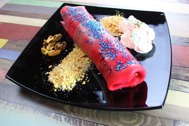 Pannkaka som fylls med chokladpralin- och banan- och kakasmulpajer på den svarta plattan med piskade kräm- och valnötstycken på t arkivbilder
