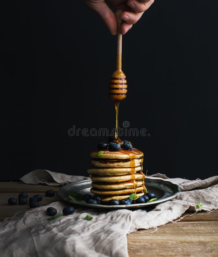 Pannkakatornet med det nya blåbäret och mintkaramellen på en lantlig metallplatta, hand håller hällande honung för träpinnen royaltyfria bilder