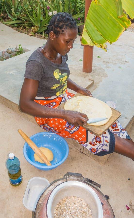 Pannkakor för Giriama kvinnamatlagning utomhus arkivfoto