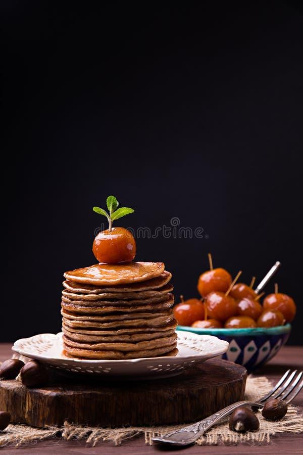 Pannkakor från kastanjebrunt mjöl med kinesiska äpplen sitter fast arkivfoto