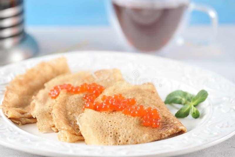 Pannkakor i en platta med kaviaren arkivfoto