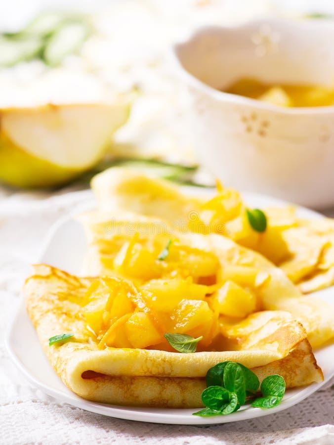 Pannkakor med apelsinen och päronsås royaltyfri bild