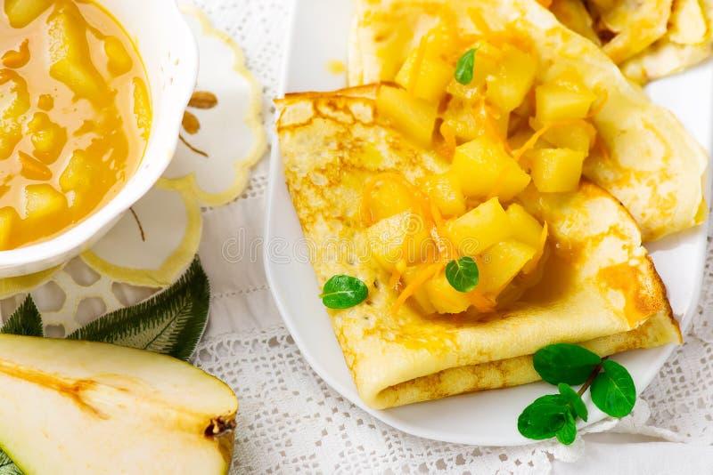 Pannkakor med apelsinen och päronsås royaltyfria foton