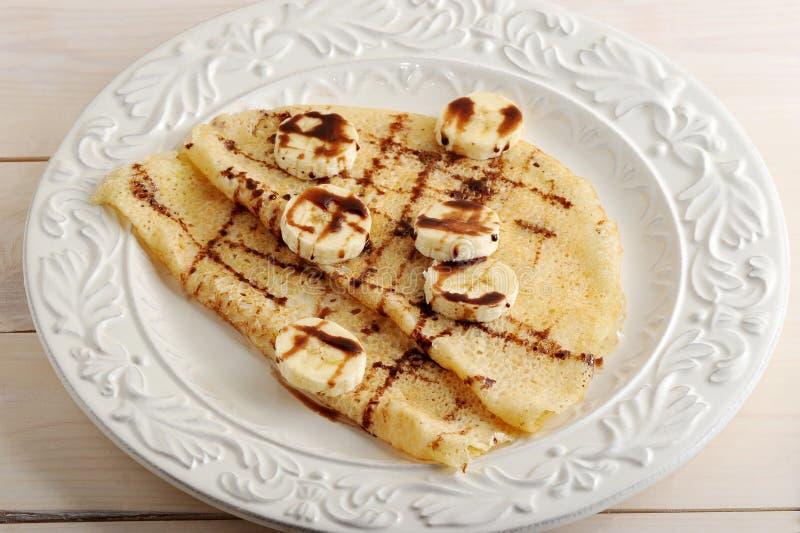 Pannkakor med bananen och choklad på en platta royaltyfri fotografi