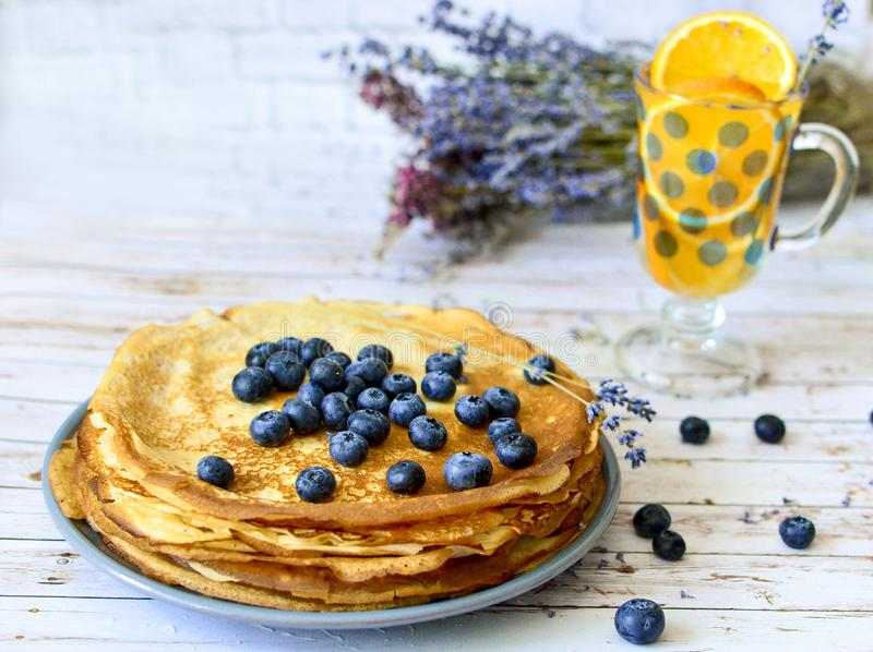 Pannkakor med blåbär spricker ut överst och orange citrus lemonad med lavendelpinnar Tunna förbaskade pannkakor Morgon arkivbilder