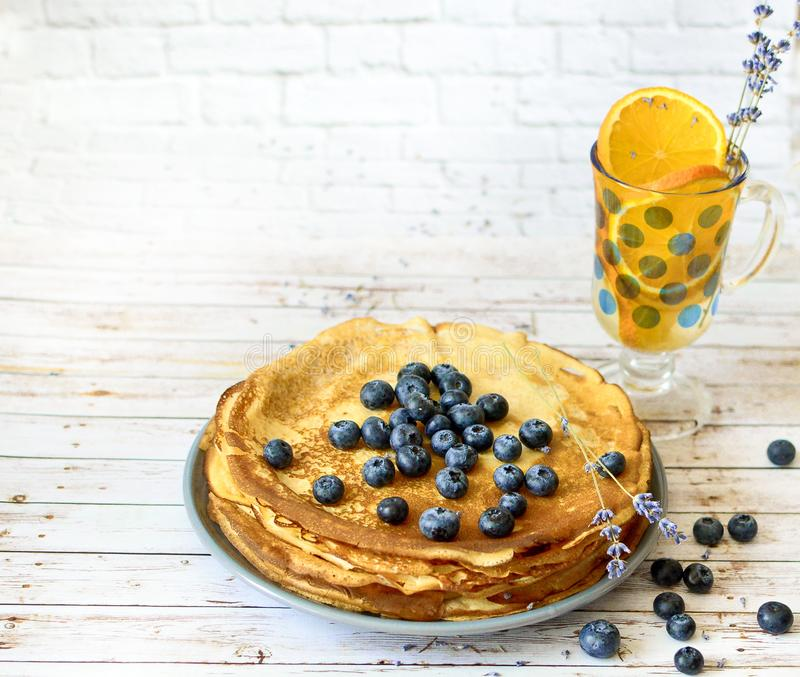 Pannkakor med blåbär spricker ut överst och orange citrus lemonad med lavendelpinnar Tunna förbaskade pannkakor Morgon royaltyfria bilder