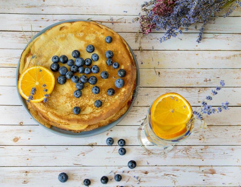 Pannkakor med blåbär spricker ut överst och orange citrus lemonad med lavendelpinnar Tunna förbaskade pannkakor Morgon arkivbild