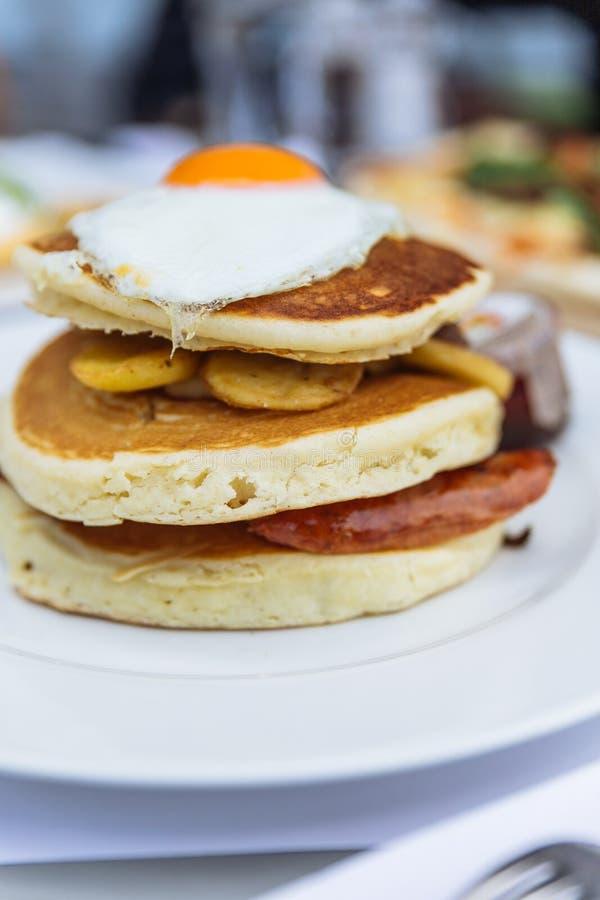 Pannkakor med djup stekt bacon, den stekte potatisen med peelen och det stekte ägget på överkanten tjänade som med lönnsirap på r fotografering för bildbyråer