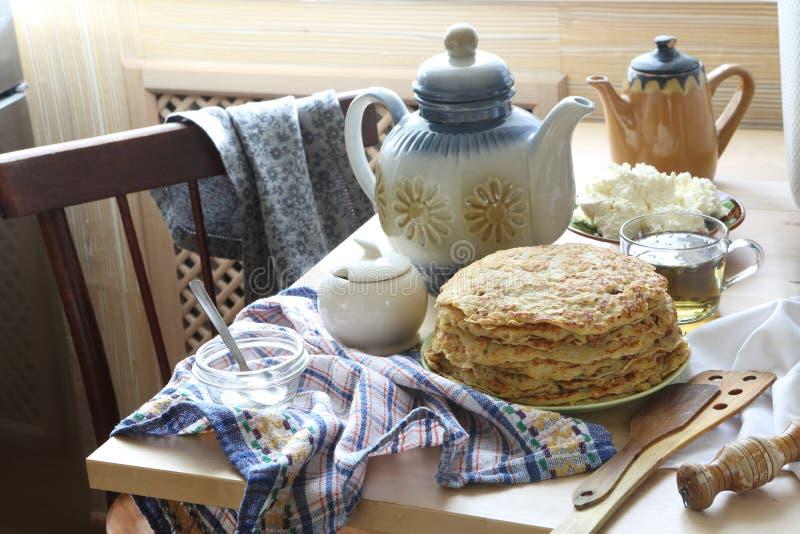 Pannkakor med gräddfil, ett nytt bär och te arkivbild