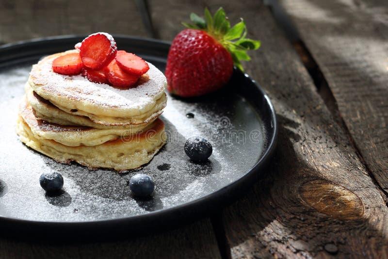 Pannkakor med jordgubbar, bl?b?r och pudrat socker s?t frukost royaltyfri foto