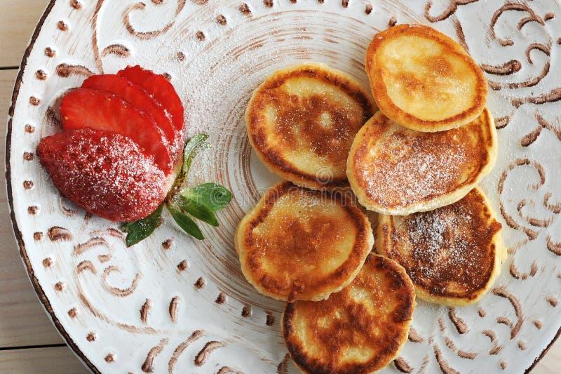 Pannkakor med jordgubbar och pudrat socker på plattan royaltyfri bild
