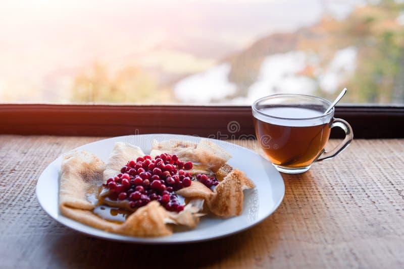 Pannkakor med lingonet och honung royaltyfri foto