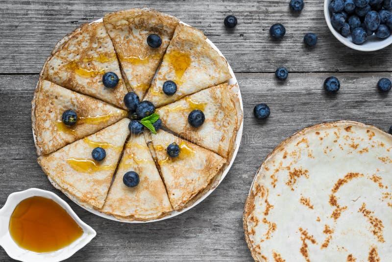 Pannkakor med ny blåbär, lönnsirap eller honung och mintkaramell för frukost arkivfoto