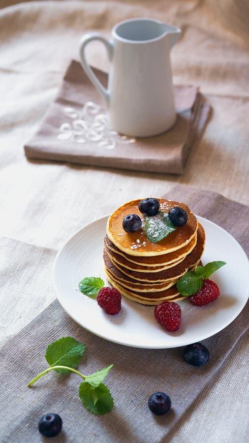 Pannkakor med skogfruktbär på den vita tabellen med mjölkar tillbringaren Nya pannkakor på plattabordduk Blåbär hallon, royaltyfri bild