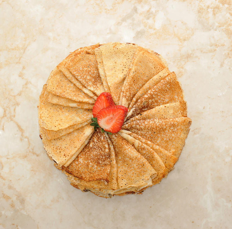 pannkakor på en platta, en vikt triangel och jordgubbar arkivbild