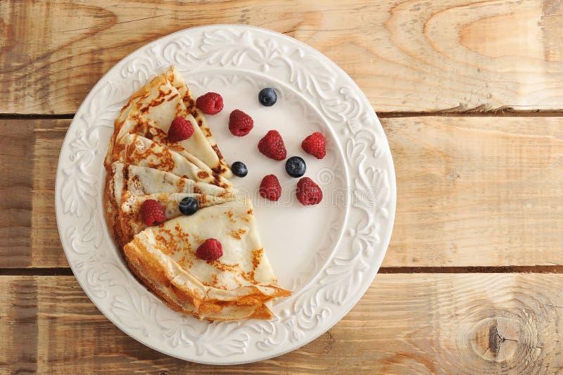 Pannkakor på en platta och bär - hallon och blåbär arkivbild