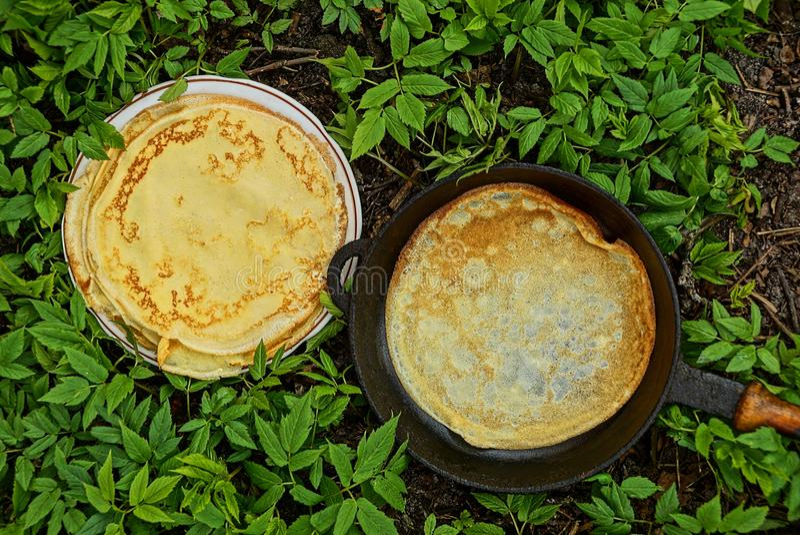 Pannkakor på en platta och en stekpanna i grön vegetation arkivfoto