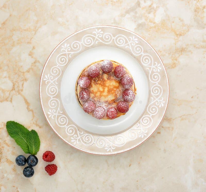 Pannkakor på plattan med bär arkivbild
