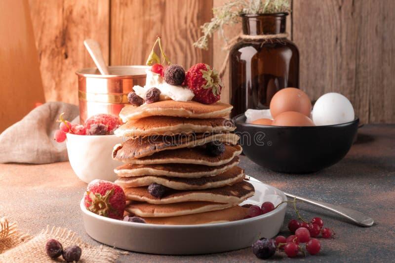 Pannkakor som staplas på den vita plattan med jordgubbar, blåbär och gräddfil royaltyfri foto