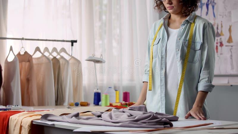 Panno spiegare del sarto da donna sulla tavola di lavoro ed attaccare i modelli, progettazione di modo fotografia stock