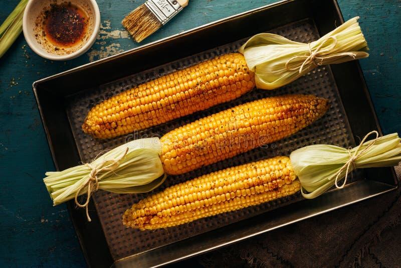 Pannocchie del mais su un vassoio di cottura con petrolio e le spezie fotografia stock libera da diritti