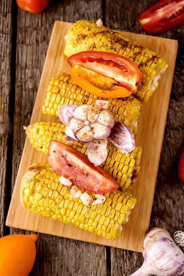 Pannocchie e pomodori di granturco arrostite con aglio e le spezie sulla vista superiore di Tray Wooden Background Vegetarian Dis fotografia stock