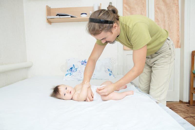 Pannolino cambiante del papà sulla neonata sul letto, pannolino cambiante, vita di tutti i giorni fotografia stock libera da diritti