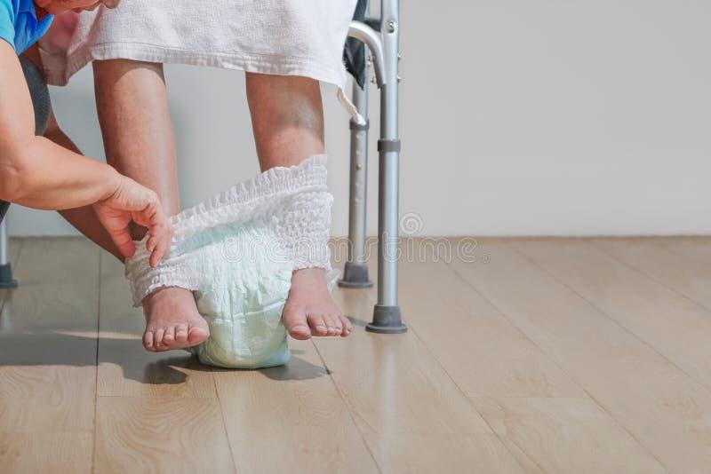 Pannolino cambiante della donna anziana con il badante fotografie stock libere da diritti
