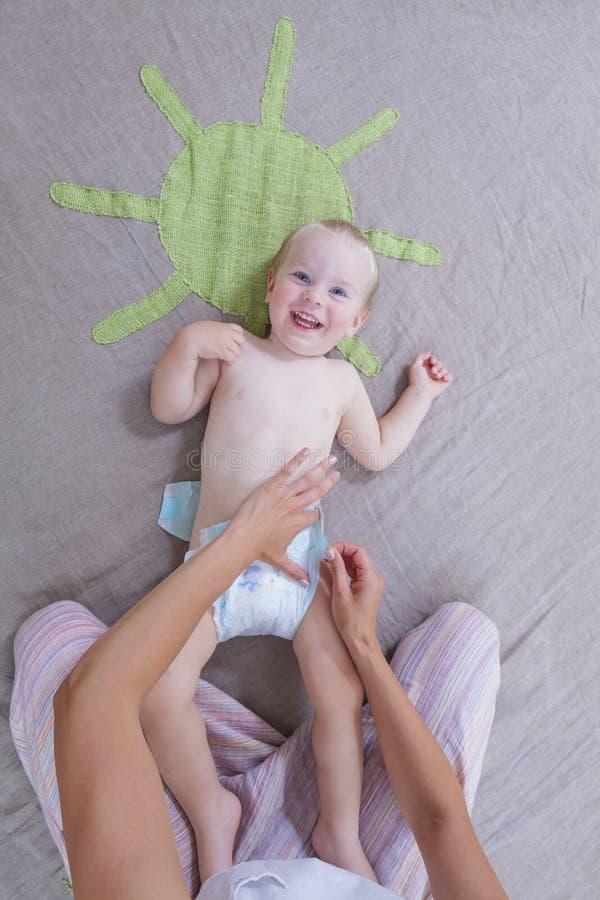 Pannolino del bambino del cambiamento del gioco del vestito dalla mamma fotografia stock