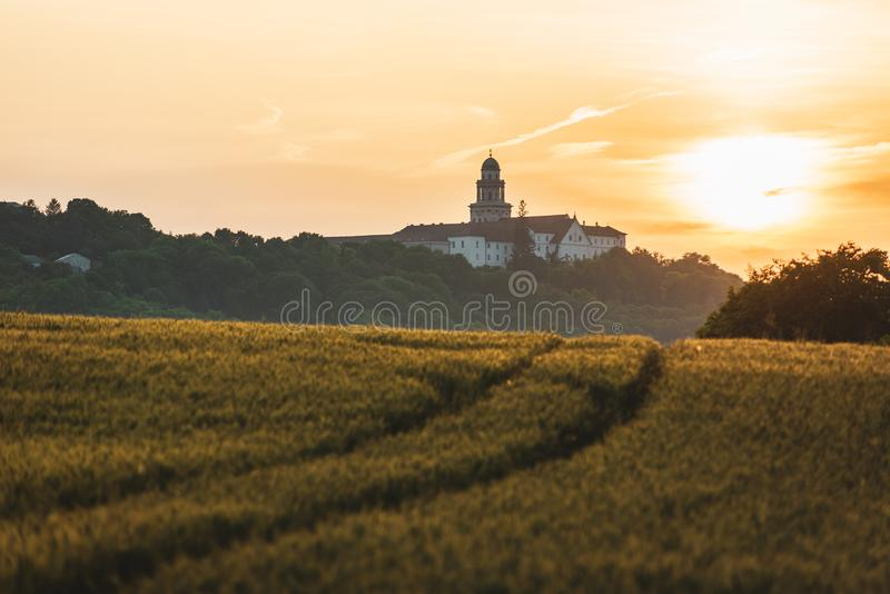Pannonhalma Archabbey with wheat field and path on sunset in Hungary. Pannonhalma Archabbey with wheat field and path on sunset time in summer royalty free stock photography