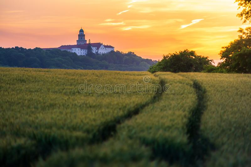 Pannonhalma Archabbey with wheat field and path on sunset in Hungary. Pannonhalma Archabbey with wheat field and path on sunset time in summer royalty free stock image