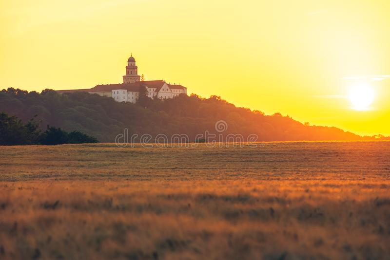 Pannonhalma Archabbey with wheat field on sunset in Hungary. Pannonhalma Archabbey with wheat field on sunset time in summer royalty free stock photos