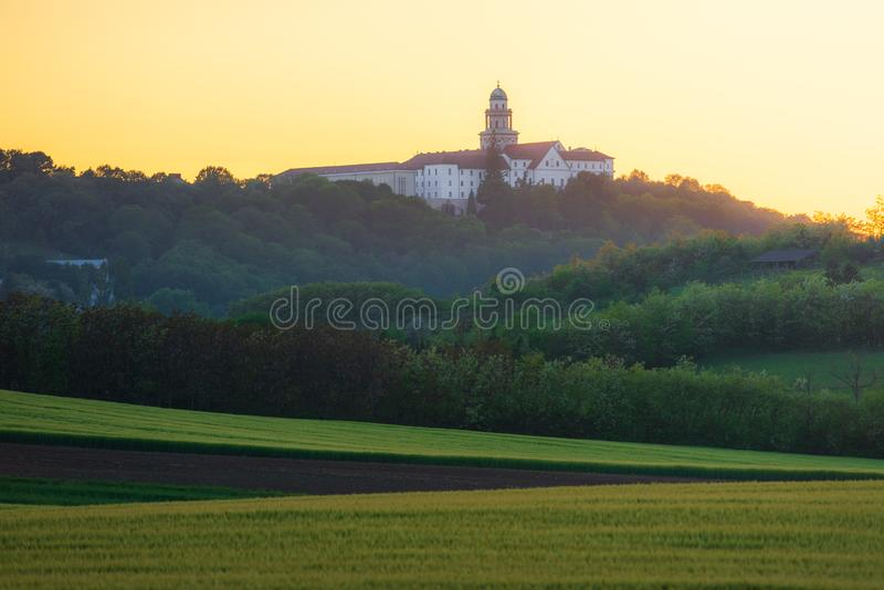 Pannonhalma Archabbey with wheat field on sunset. Time in spring royalty free stock image