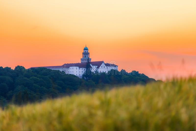 Pannonhalma Archabbey with wheat field on sunset in Hungary. Pannonhalma Archabbey with wheat field on sunset time in summer royalty free stock photo