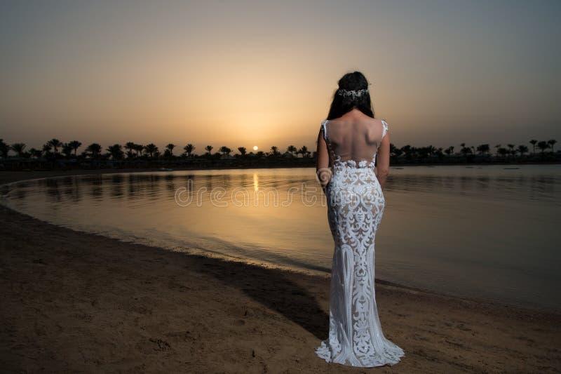 Panny młodej ślubnej sukni biały stojak na piaskowatej plaży smokingowy czerepu rozkazu ?lub Panna młoda szczęśliwa cieszy się zm zdjęcie stock