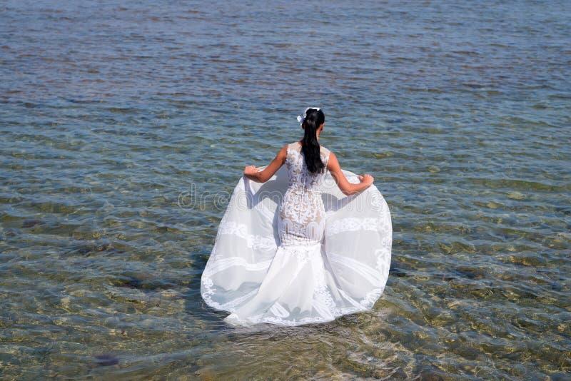 Panny młodej ślubnej sukni biały stojak w wodzie morskiej Mokry ślubnej sukni gorący słoneczny dzień Panna młoda szczęśliwa ciesz fotografia stock