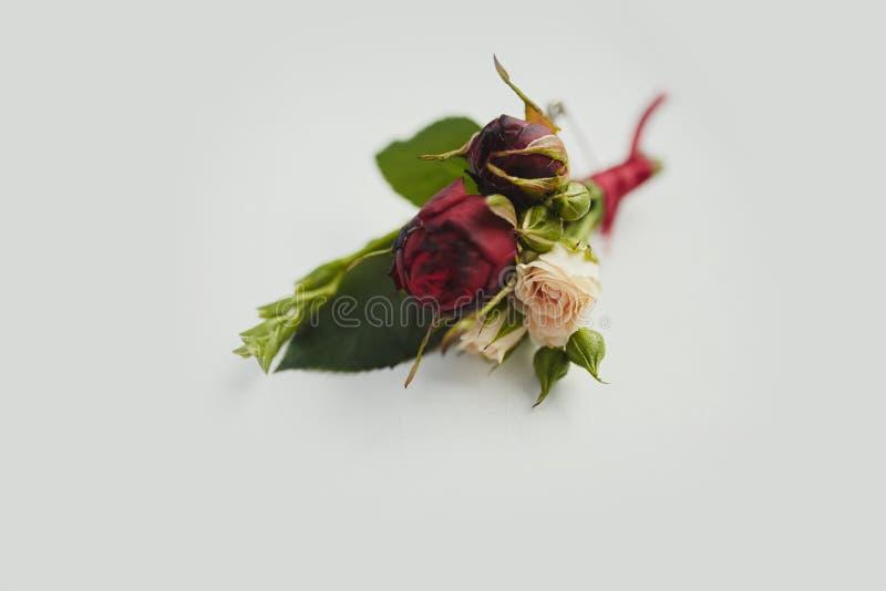 Panny młodej mienie w ręce w górę fornala buttonhole kwitnie z białymi różami, zieleń i greenery, fotografia stock