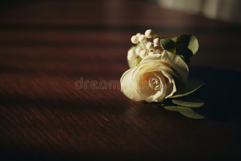Panny młodej mienie w ręce w górę fornala buttonhole kwitnie z białymi różami, zieleń i greenery, zdjęcie royalty free