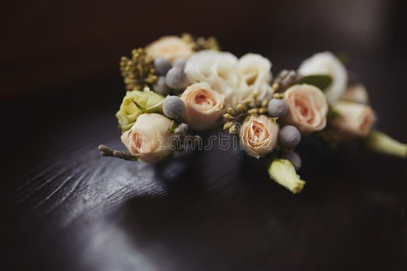 Panny młodej mienie w ręce w górę fornala buttonhole kwitnie z białymi różami, zieleń i greenery, obraz stock