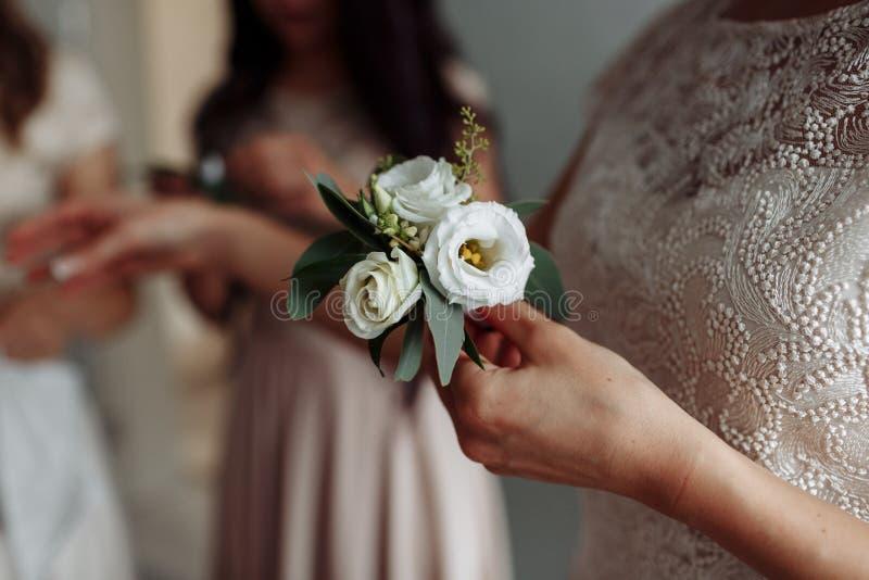 Panny młodej mienie w ręce w górę fornala buttonhole kwitnie z białymi różami, zieleń i greenery, zdjęcia royalty free