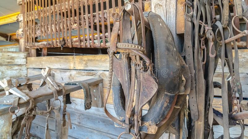 Pano Close up of old and dirty horse saddle with rusty metal and damaged leather. Deteriorated and abandoned horse riding equipment inside a rustic barn royalty free stock photo