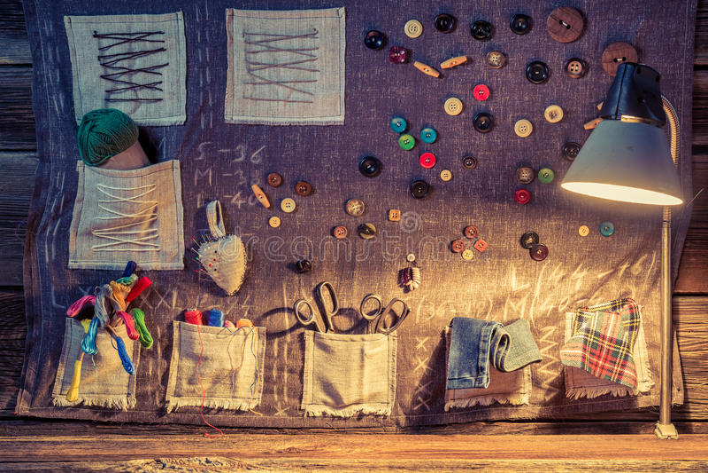 Pano da costura com tesouras, linhas e agulhas na oficina do alfaiate ilustração do vetor