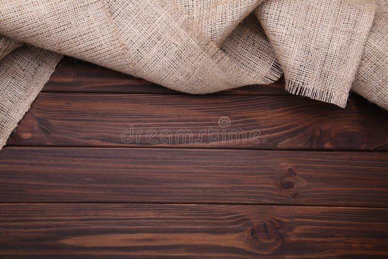 Pano de saco natural no fundo de madeira marrom Lona na tabela de madeira marrom imagem de stock royalty free