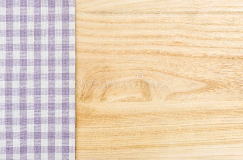 Pano de tabela quadriculado roxo em um fundo de madeira imagens de stock royalty free