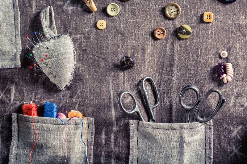 Pano feito a mão da costura com tesouras, linhas e agulhas na oficina do alfaiate ilustração stock